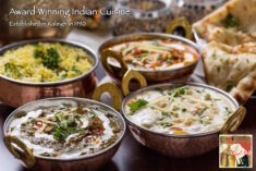 Vegetarian and non-vegetarian Indian food displayed in dishes along with naan bread.