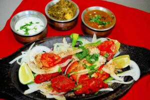 Chicken and shrimp cooked in tandoori style, displayed on a skewer along with vegetable entrees and raita sauce