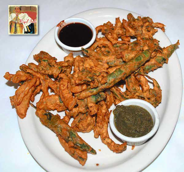 Indian appetizer pakora displayed with sauce in a plate.